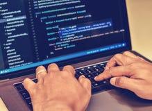 Primo piano delle mani di un programmatore che scrivono i codici sorgente immagini stock libere da diritti
