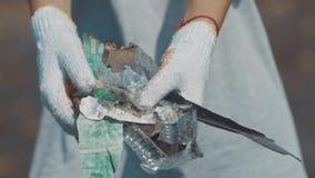 Primo piano delle mani di un volontario che mostra rifiuti di plastica raccolti sulla spiaggia dell'oceano Volontari che puliscon archivi video