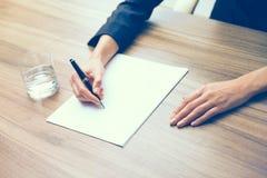 Primo piano delle mani di una donna di affari mentre annotando alcune informazioni essenziali Un bicchiere d'acqua, carta e una p Fotografia Stock Libera da Diritti
