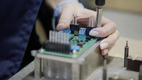 Primo piano delle mani delle donne nella fabbrica durante il montaggio dell'apparecchio elettronico Primo piano delle componenti  stock footage