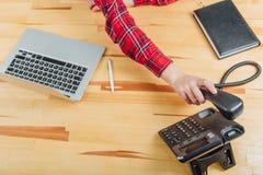 Primo piano delle mani delle donne in un ufficio con un telefono in loro mani che si trovano sulla tavola, posto di lavoro Contro fotografia stock libera da diritti