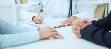 Primo piano delle mani e di medico dei pazienti che prendono le note Concetto di salute di giovane famiglia Fotografie Stock Libere da Diritti