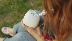 Primo piano delle mani femminili che ricavano un modello con pittura da un tubo su una tazza bianca La ragazza dipinge l'ornament archivi video