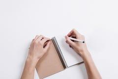 Primo piano delle mani femminili che scrivono in blocco note con una penna su un tabl Fotografie Stock