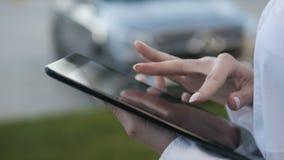 Primo piano delle mani femminili che scrivono sulla compressa di Digital del touch screen all'aperto Immagine Stock