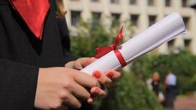 Primo piano delle mani femminili che tengono diploma con il nastro rosso, graduation archivi video