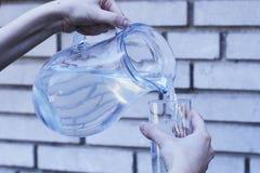 Primo piano delle mani femminili che versano acqua da una caraffa di vetro nella a fotografie stock