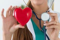 Primo piano delle mani femminili di medico che tengono cuore e stethosco colti Immagine Stock Libera da Diritti