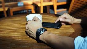 Primo piano delle mani maschii asiatiche che giocano smartphone e che bevono caffè ad una tavola all'aperto con luce solare di ma immagine stock