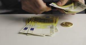 Primo piano delle mani maschii che contano duecento euro fatture video d archivio