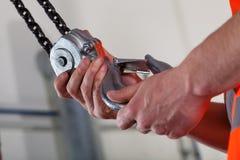 Primo piano delle mani maschii e del gancio di sollevamento Fotografia Stock Libera da Diritti