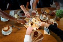 Primo piano delle mani multirazziali con i dessert e le tazze di caffè in un caffè fotografia stock libera da diritti