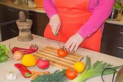 Primo piano delle mani umane che cucinano alimento, insalata delle verdure Preparazione del pasto fresco nella cucina Immagine Stock