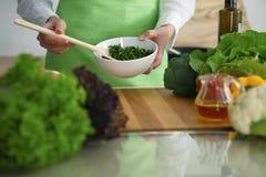 Primo piano delle mani umane che cucinano l'insalata delle verdure in cucina sulla tavola di vetro con la riflessione Fotografie Stock Libere da Diritti