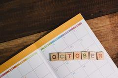 Primo piano delle mattonelle di alfabeto di OTTOBRE sul calendario del libro del pianificatore sulla tavola di legno Fotografie Stock Libere da Diritti