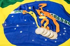 Primo piano delle medaglie d'oro sulla bandiera brasiliana Immagini Stock