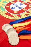 Primo piano delle medaglie d'oro sulla bandiera del Portoghese Fotografia Stock