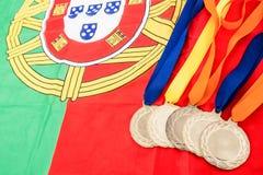 Primo piano delle medaglie d'oro sulla bandiera del Portoghese Fotografie Stock Libere da Diritti