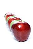 Primo piano delle mele nella fila su fondo bianco Immagini Stock Libere da Diritti