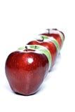 Primo piano delle mele nella fila su fondo bianco Fotografia Stock Libera da Diritti