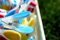 Primo piano delle mollette da bucato brillantemente colorate in un contenitore su erba, Fotografia Stock