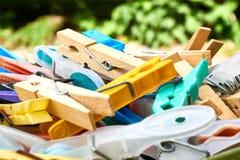 Primo piano delle mollette da bucato di plastica e di legno in un canestro immagine stock
