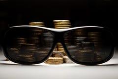 Primo piano delle monete dietro le paia degli occhiali da sole Fotografie Stock