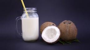Primo piano delle noci di cocco marroni organiche e di un barattolo di muratore con latte di cocco naturale e una paglia gialla s Fotografia Stock