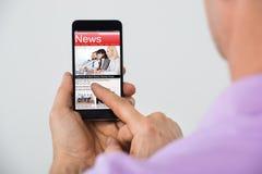 Primo piano delle notizie della lettura dell'uomo su Smartphone fotografia stock