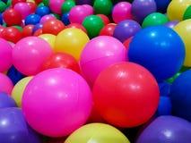 Primo piano delle palle di plastica colorate in stagno della stanza del gioco immagini stock
