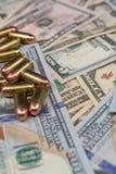 Primo piano delle pallottole su un mucchio di valuta degli Stati Uniti fotografia stock