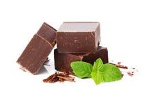 Primo piano delle parti del cioccolato e delle foglie di menta su bianco fotografie stock libere da diritti
