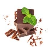 Primo piano delle parti del cioccolato e delle foglie di menta fotografia stock