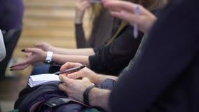 Primo piano delle penne di tenuta delle mani e delle note di fabbricazione alla conferenza archivi video