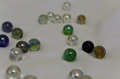 Primo piano delle perle multicolori di Natale su una tela bianca con un fondo vago molle Le perle sono sparse in un manne caotico immagine stock libera da diritti
