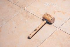 Primo piano delle piastrelle per pavimento, sugli incroci delle mattonelle delle mattonelle e sul maglio bianchi di plastica dell immagini stock