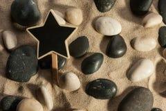 Primo piano delle pietre e stella che attacca dalla sabbia nel sunl Immagine Stock