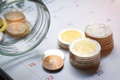 Primo piano delle pile dei soldi di baht tailandese su un calendario stampato con i numeri in nero ed in rosso su fondo nero Conc fotografia stock