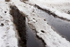 Primo piano delle pozze enormi di neve sulle vie della città immagini stock