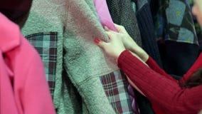 Primo piano delle ragazze che scelgono i vestiti in un deposito Comperando sul sito video d archivio