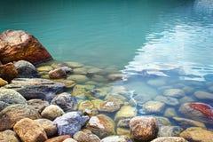 Primo piano delle rocce in acqua a Lake Louise Immagini Stock Libere da Diritti