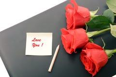 Primo piano delle rose rosse su un computer portatile immagini 3d isolate su priorità bassa bianca Fotografia Stock
