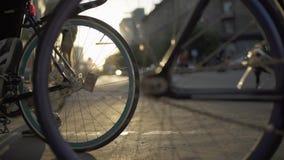 Primo piano delle ruote di bicicletta alla via della città di tramonto Trasporto urbano ecologico stock footage