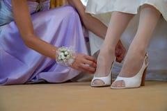 Primo piano delle scarpe del ` s della sposa e delle mani bianche del ` s della damigella d'onore Mattina r immagini stock