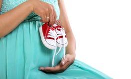 Primo piano delle scarpe di bambino incinte della tenuta della mano del ` s della mamma fotografie stock