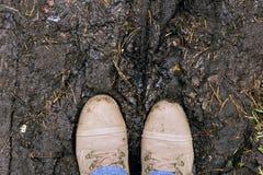 Primo piano delle scarpe sulla strada fangosa Fotografia Stock