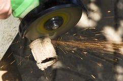 Primo piano delle scintille dalla smerigliatrice di angolo Processo di taglio del tubo del metallo immagine stock libera da diritti