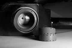 Primo piano delle strisce di pellicola con la macchina fotografica d'annata del cinema di film con la lente su fondo Fotografia Stock