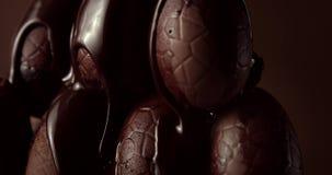 Primo piano delle uova di cioccolato e del cioccolato liquido di caduta su  video d archivio