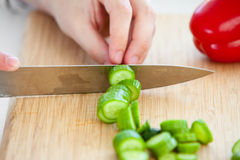 Primo piano delle verdure di taglio dell'uomo in cucina Fotografia Stock Libera da Diritti